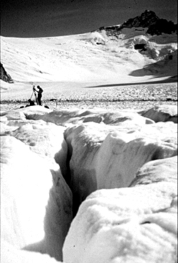 A crevasse on a glacier with researchers and equipment in the background.
