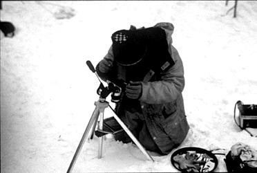 A close up of the same researcher photographing glacier ice crystals.
